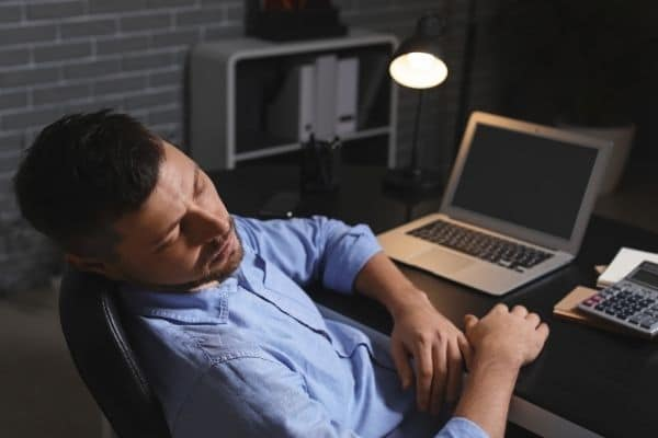 man sleeping in front of a laptop